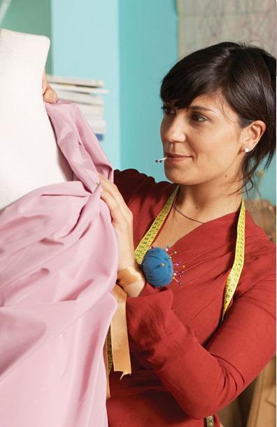 Female fashion designer working on dress on mannequin